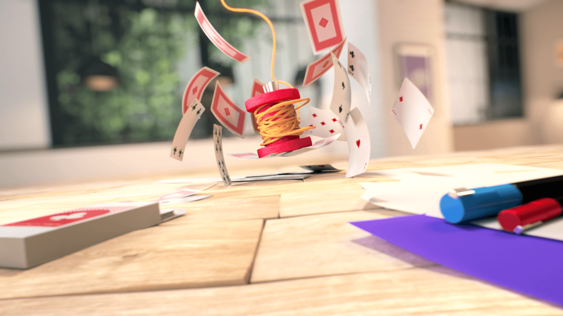 Spool of 3D plasticine thread falling on a deck of playing cards